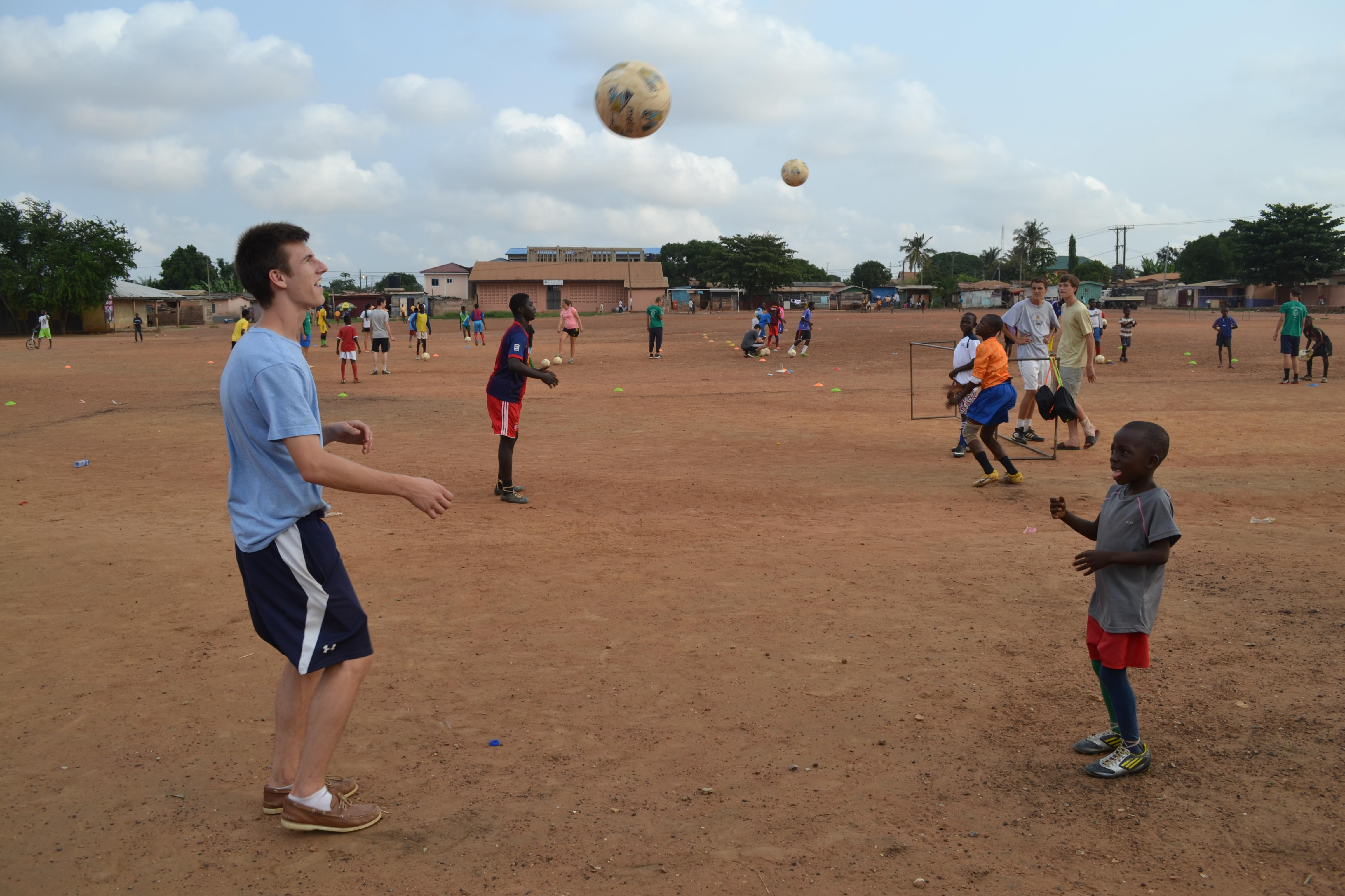 Projects Abroad volunteers taking part in football coaching for high school students in Ghana lead a ball skills practice session with a young team.